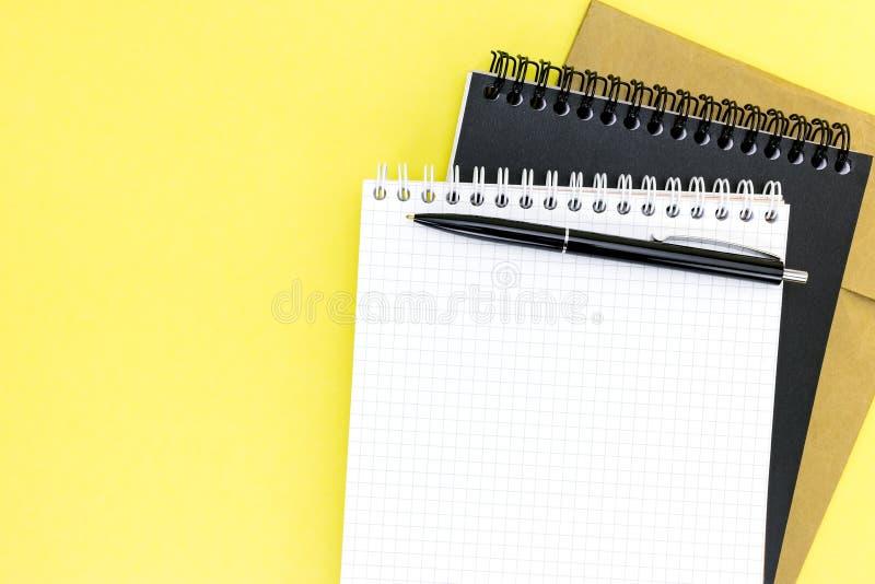 Żółty desktop z otwartym ciosowym notepad, notatnikami i piórem, obrazy stock