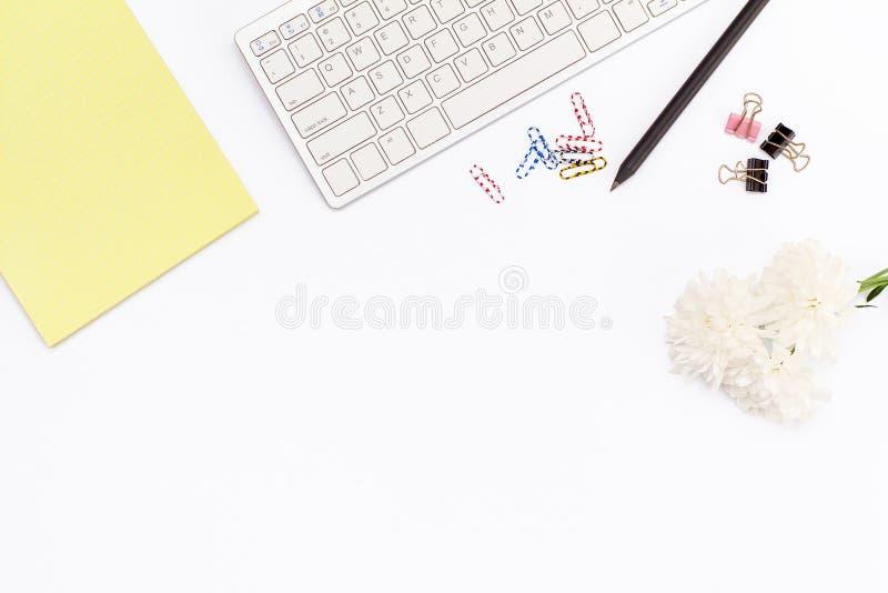 Żółty legalny ochraniacz, klawiatura, papierowe klamerki, ołówek i chryzantema, kwitniemy na białym tle Mieszkania nieatutowy poj fotografia stock