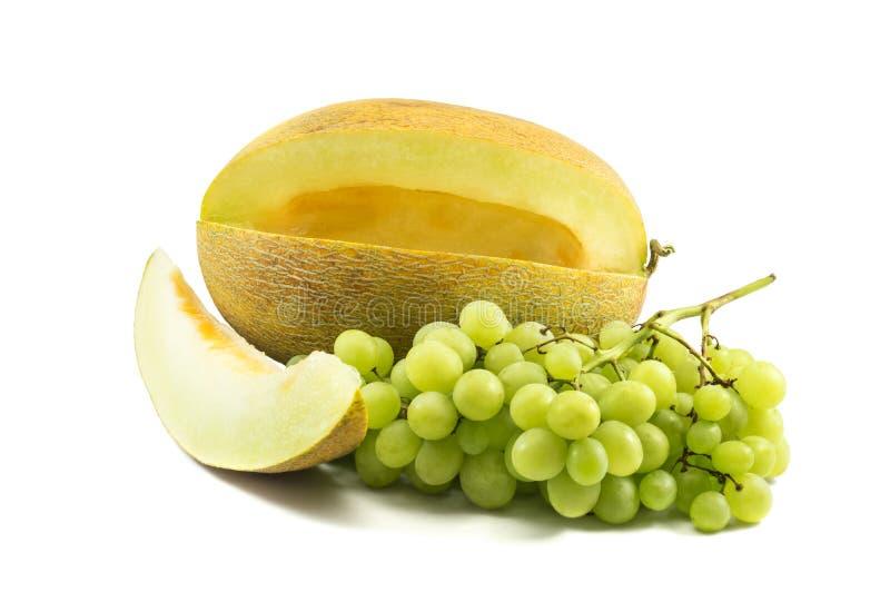 Żółty melon z plasterkiem i winogrona nad bielem zdjęcia royalty free