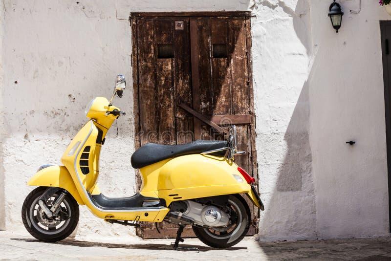 Żółty motocykl przed domowym antykwarskim drewnianym drzwi fotografia stock