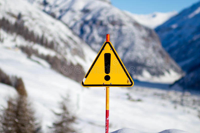 Żółty niebezpieczeństwo znak na Śnieżnej górze obrazy stock
