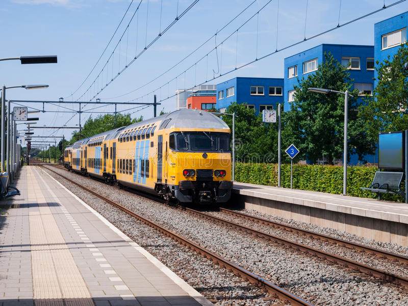 Żółty pociąg przyjeżdża przy pustą stacją fotografia stock
