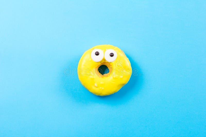 Żółty round pączek z oczami na błękitnym tle Mieszkanie nieatutowy, odgórny widok zdjęcie royalty free