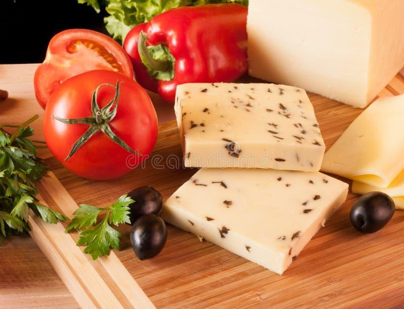 Żółty ser z oliwką na tnącej desce obrazy stock