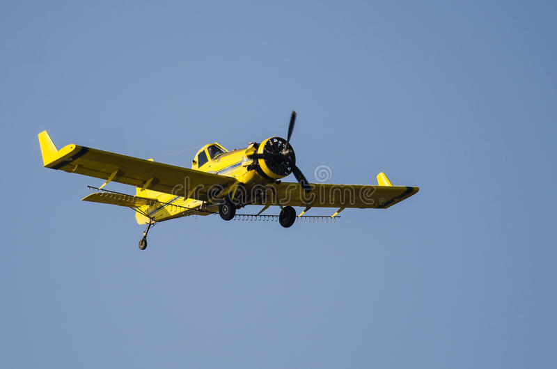 Żółty uprawy okurzania samolotu latanie w niebieskim niebie obraz royalty free