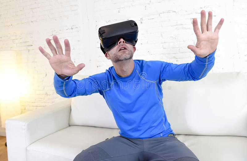 Óculos de proteção 3d de utilização entusiasmado do sofá feliz do sofá da sala de visitas do homem em casa que olham a realidade  fotos de stock royalty free