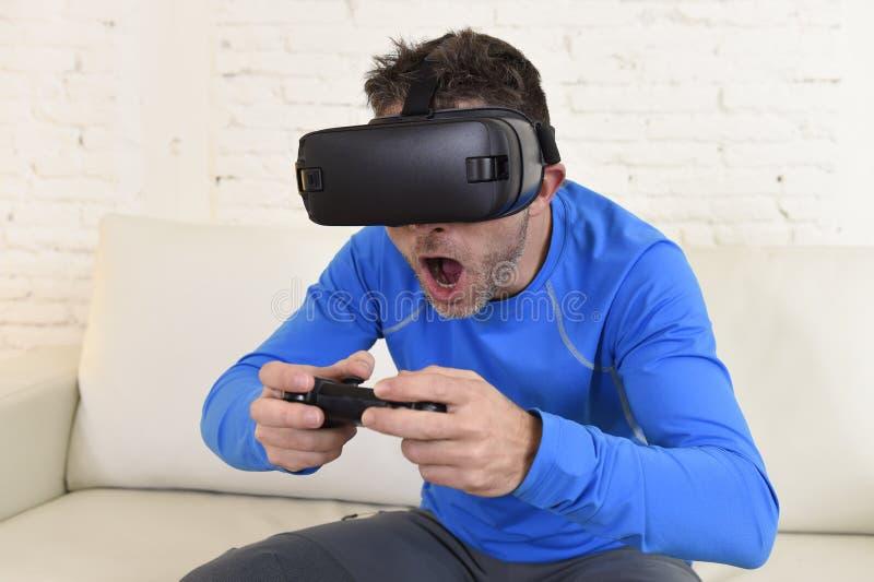 Óculos de proteção 3d de utilização entusiasmado do sofá feliz do sofá da sala de visitas do homem em casa que olham a realidade  foto de stock