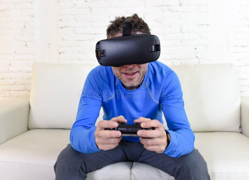 Óculos de proteção 3d de utilização entusiasmado do sofá feliz do sofá da sala de visitas do homem em casa que olham a realidade  imagens de stock royalty free