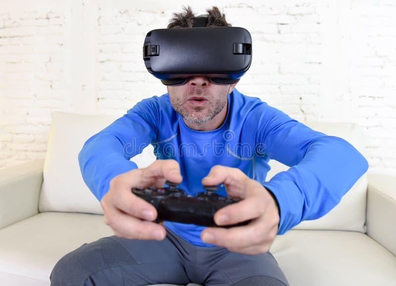 Óculos de proteção 3d de utilização entusiasmado do sofá feliz do sofá da sala de visitas do homem em casa que olham a realidade  imagens de stock