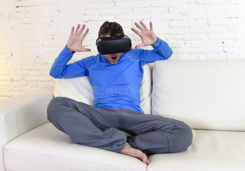 Óculos de proteção 3d de utilização entusiasmado do sofá feliz do sofá da sala de visitas do homem em casa que olham a realidade  fotografia de stock