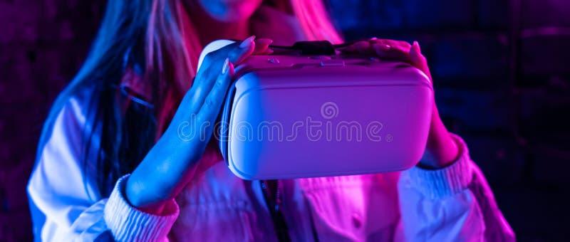Óculos de proteção dos vidros do vr da posse do gamer da menina na luz de néon roxa futurista, bandeira fotos de stock royalty free