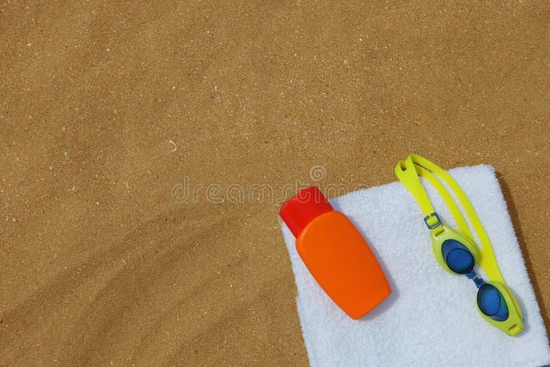 Óculos de proteção e sunblock no beachtowel fotografia de stock royalty free