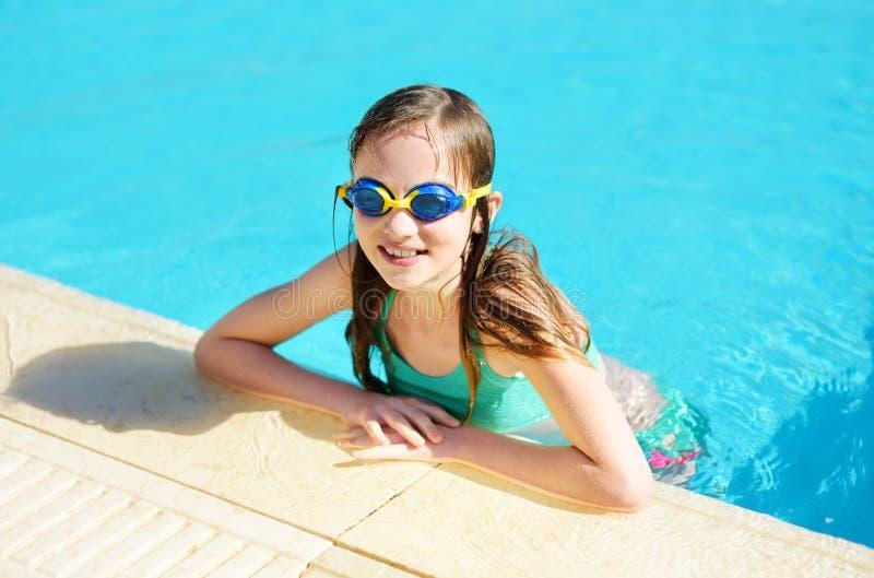 Óculos de proteção nadadores vestindo da moça bonito que têm o divertimento na associação exterior Aprendizagem nadar Criança que fotografia de stock royalty free