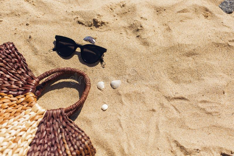 Óculos de sol à moda, saco da palha no Sandy Beach com conchas do mar, vista superior com espaço da cópia Férias de verão e conce imagens de stock
