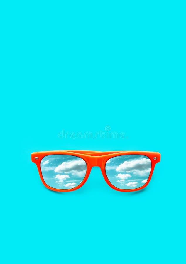 Óculos de sol alaranjados com o céu azul com reflexões das nuvens isolado no fundo azul ciano vertical Conceito do verão imagens de stock