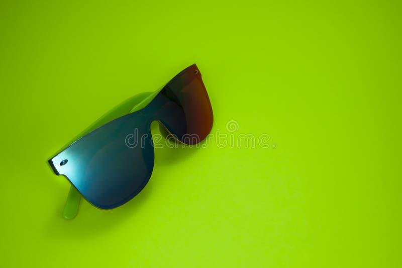 Óculos de sol coloridos modernos no fundo amarelo imagens de stock