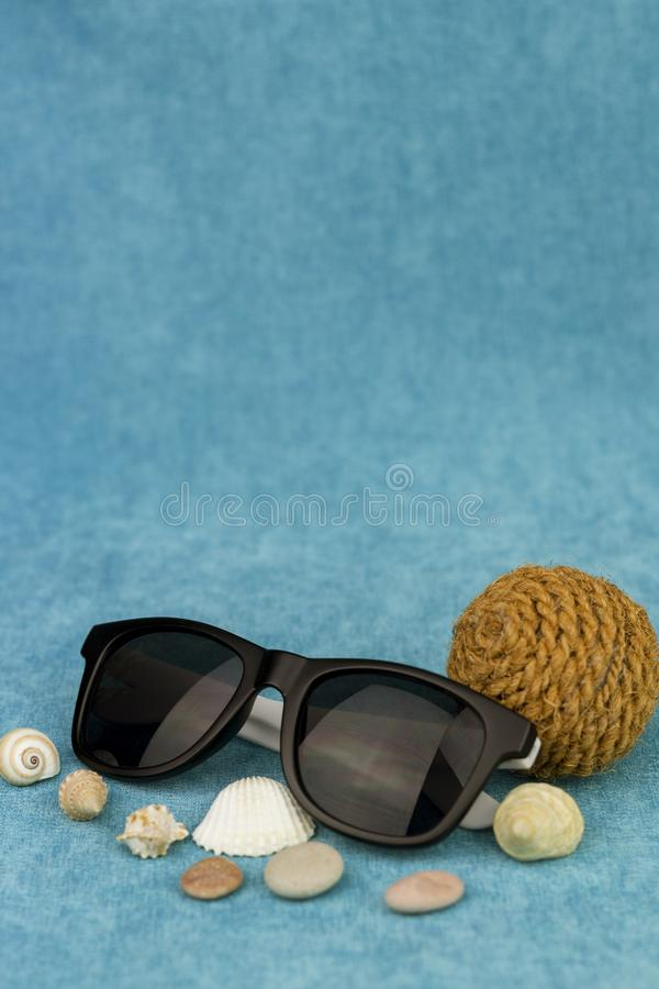Óculos de sol com conchas do mar e uma bola da corda imagens de stock royalty free