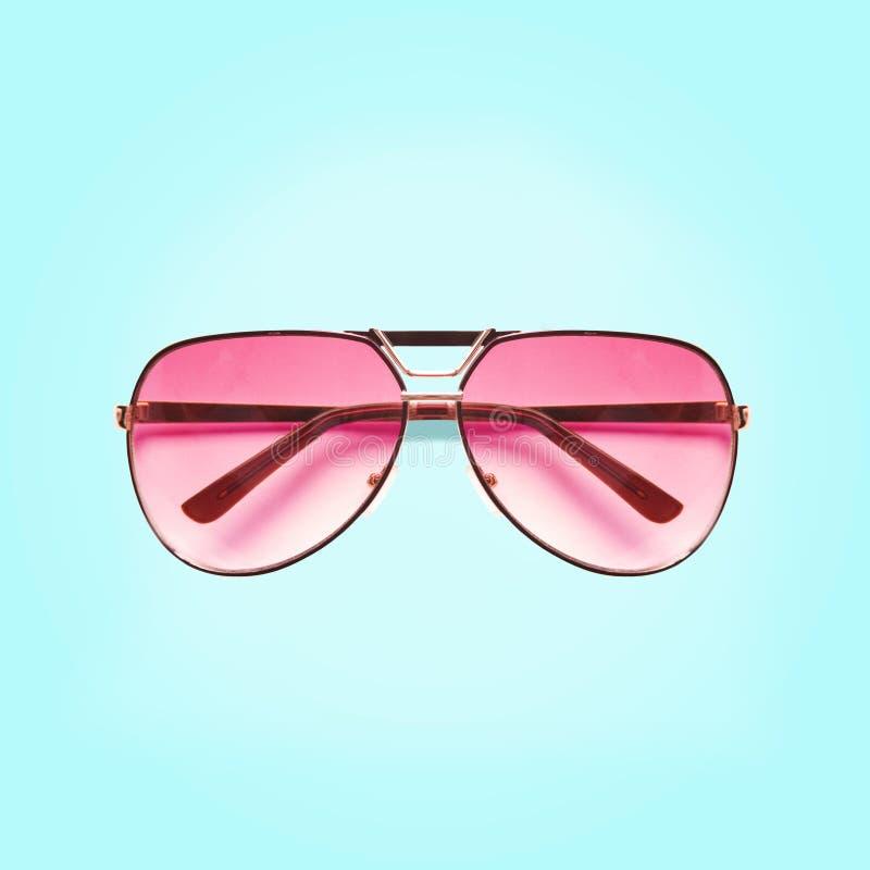 Óculos de sol cor-de-rosa isolados no fundo azul imagem de stock