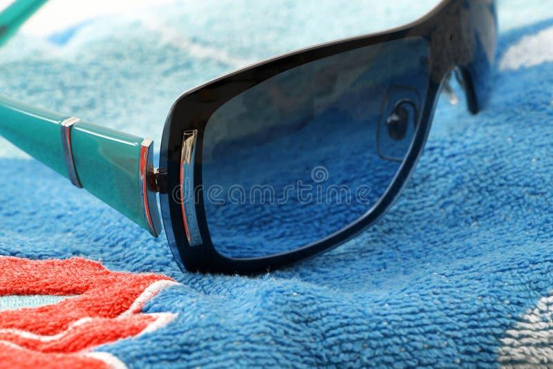 óculos de sol da forma em uma toalha de praia fotografia de stock