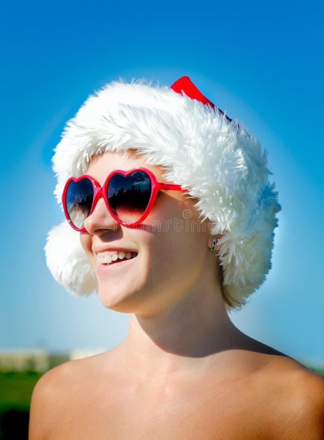 Óculos de sol dados forma coração vestindo da menina de Santa fotografia de stock