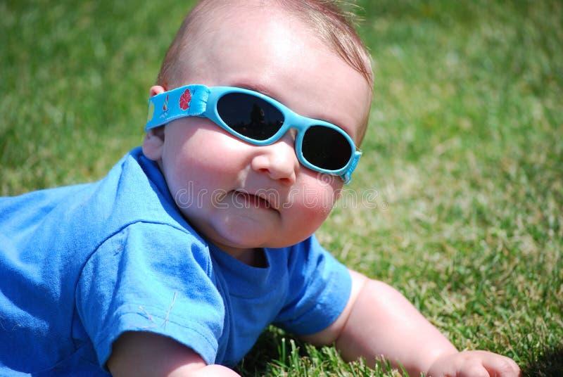 Óculos de sol desgastando do bebé que colocam na grama imagens de stock royalty free