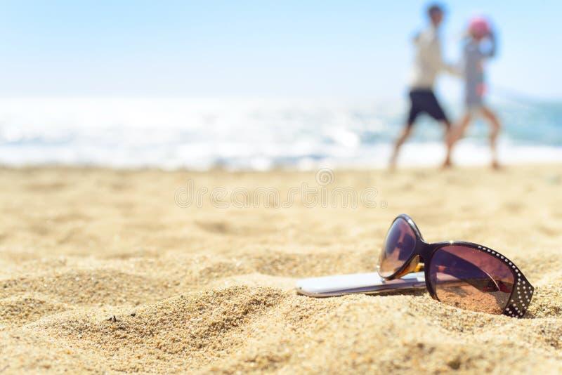 Óculos de sol e telefone na praia com os povos no fundo imagem de stock royalty free
