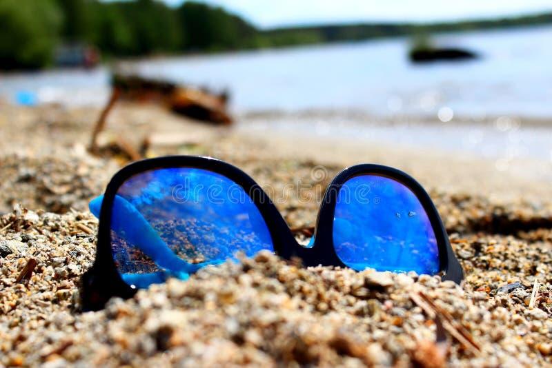 Óculos de sol em uma praia bonita fotografia de stock