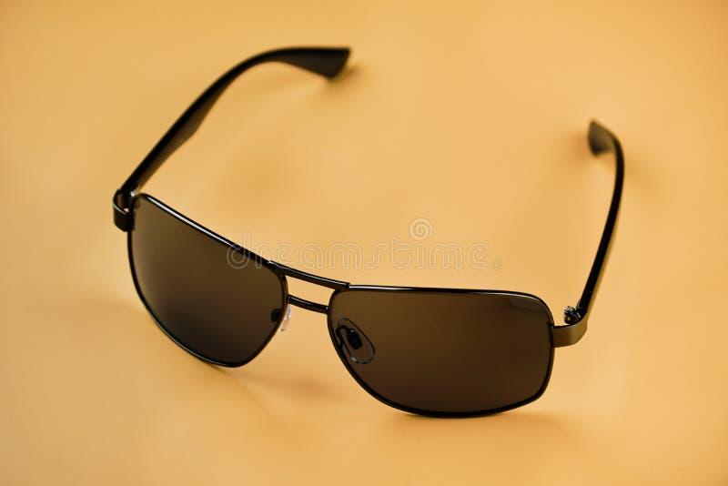 Óculos de sol isolados no fundo da cor da areia imagens de stock royalty free