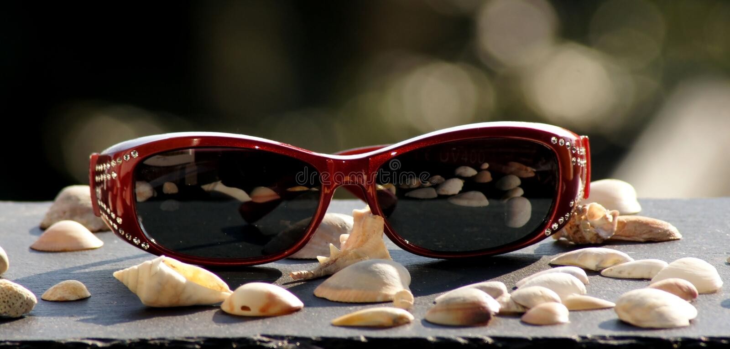 Óculos de sol na luz solar para a mulher imagens de stock