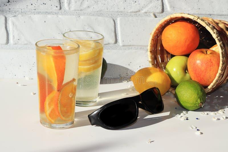 Óculos de sol pretos ao lado do suco da laranja e de limão, fruto em uma cesta imagens de stock