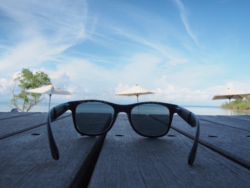 Óculos de sol pretos colocados em uma placa de madeira na praia no fundo das nuvens fotografia de stock royalty free