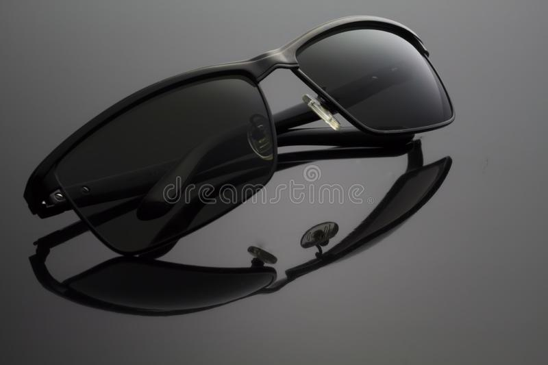 Óculos de sol pretos dobrados no fundo preto imagens de stock