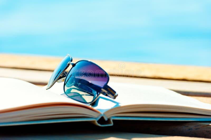 Óculos de sol que encontram-se em um livro aberto foto de stock