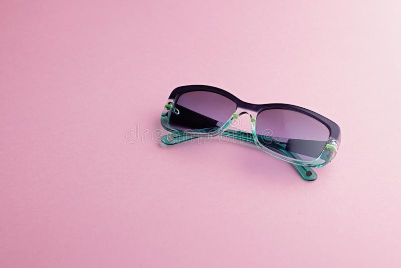 Óculos de sol retangulares elegantes com o close up dos matizes do inclinação no fundo cor-de-rosa imagens de stock royalty free