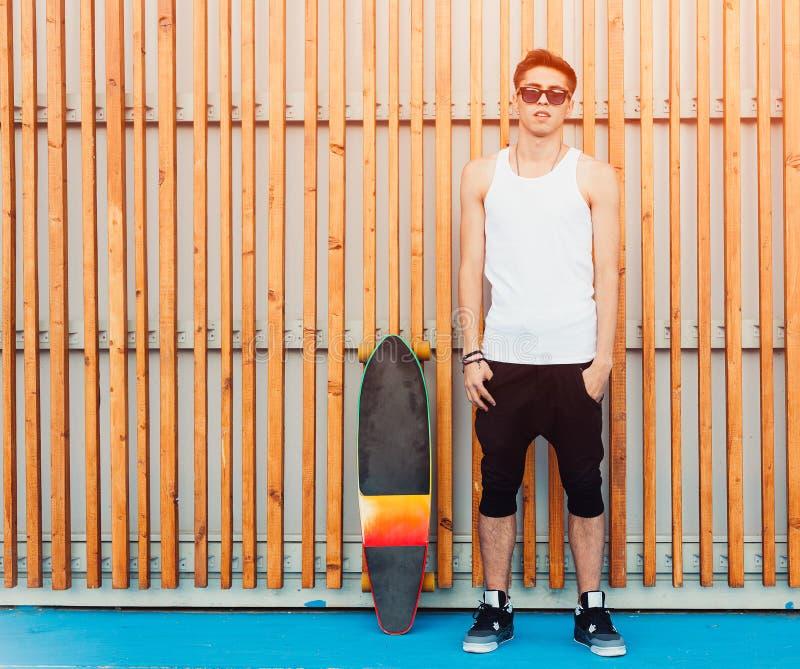 Óculos de sol urbanos e skate do homem que levantam no fundo de madeira das pranchas Bonito Indivíduo fresco Camisa branca vestin fotos de stock