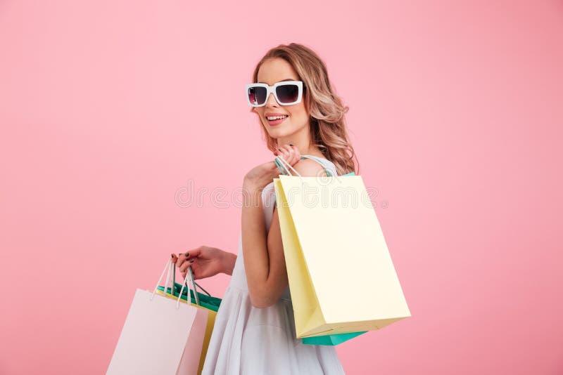 Óculos de sol vestindo da jovem mulher feliz que guardam sacos de compras foto de stock royalty free