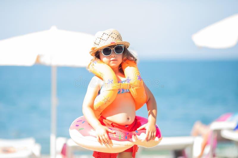 Óculos de sol vestindo da menina adorável, flutuadores infláveis das sobre-luvas e anel inflável do flutuador da filhós, costa de imagens de stock royalty free