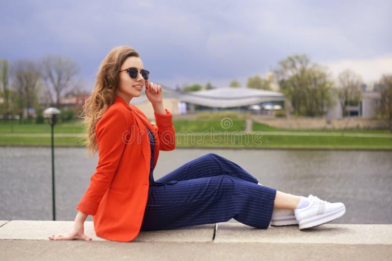 Óculos de sol vestindo da menina bonita no beira-rio Menina que senta-se no cais e no lookingat o rio Moças bonitas fora fotos de stock royalty free