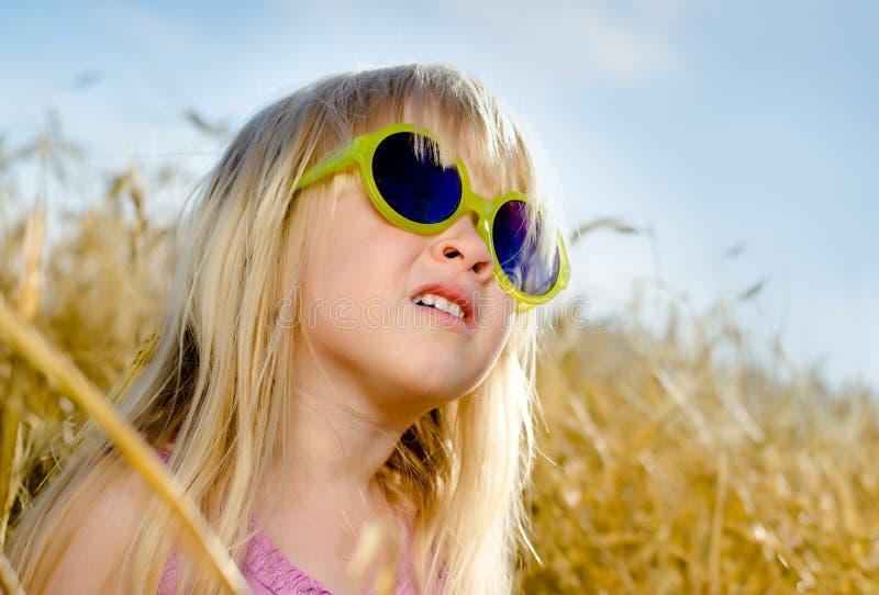 Óculos de sol vestindo da menina bonito, em um dia morno foto de stock royalty free