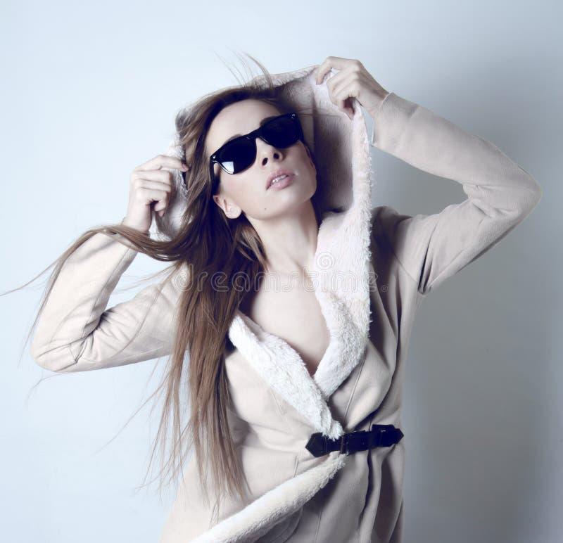 Óculos de sol vestindo da menina e um casaco de pele branco fotografia de stock