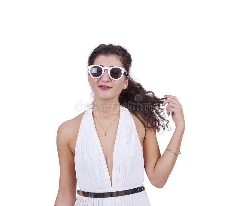 Óculos de sol vestindo da mulher atrativa contra o branco imagens de stock