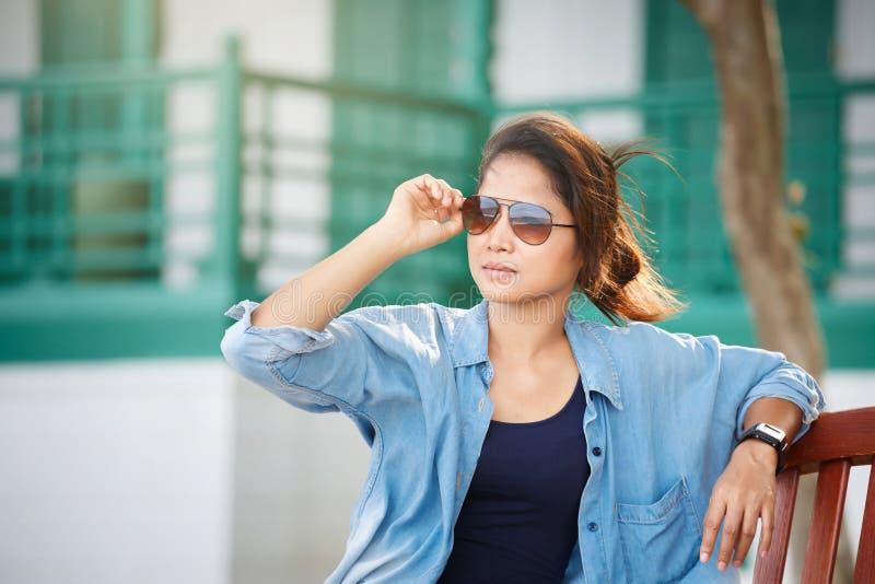Óculos de sol vestindo da mulher, calças de brim vestindo e um revestimento da sarja de Nimes ela imagens de stock