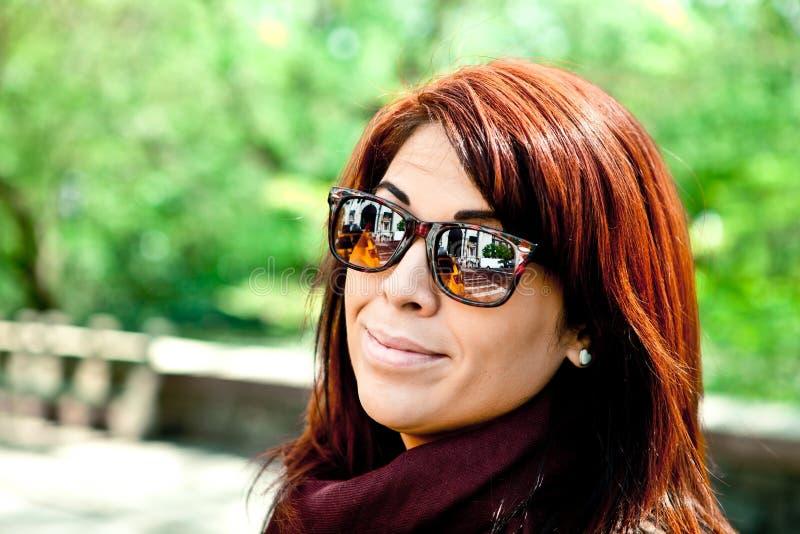 Óculos de sol vestindo da mulher do Redhead fotografia de stock royalty free
