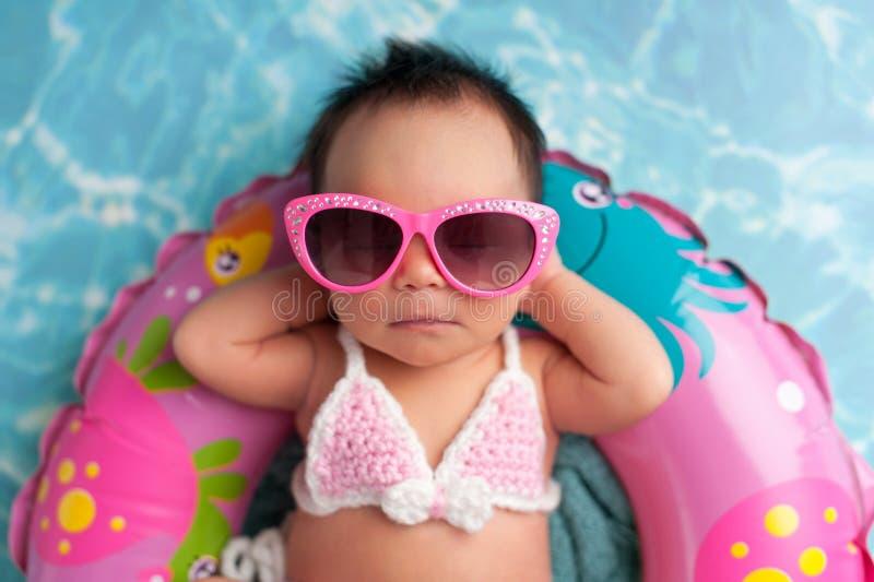 Óculos de sol vestindo do bebê recém-nascido e uma parte superior de biquini imagem de stock