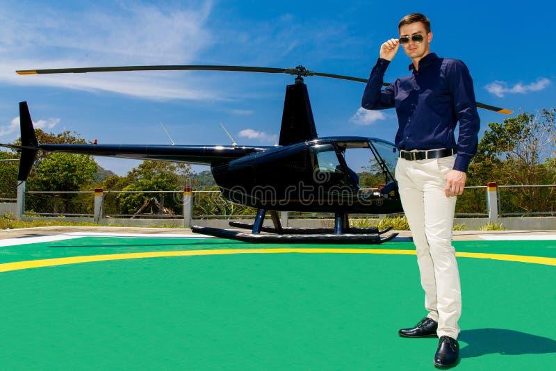 Óculos de sol vestindo do homem elegante novo que estão ao lado de um privado imagens de stock royalty free
