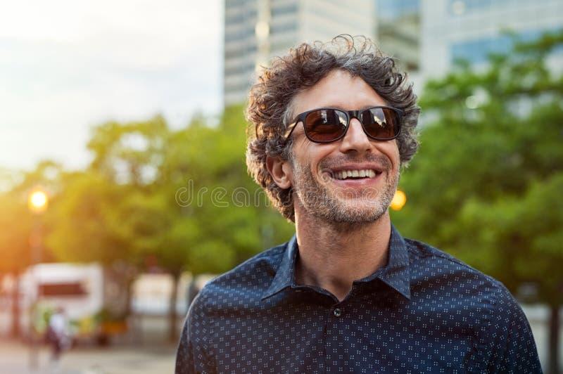 Óculos de sol vestindo do homem feliz fotografia de stock