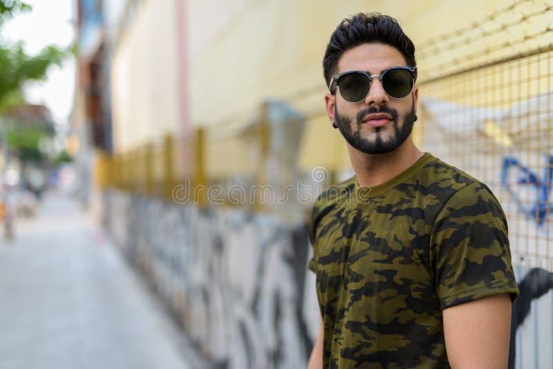 Óculos de sol vestindo do homem indiano considerável novo ao pensar o agai fotografia de stock