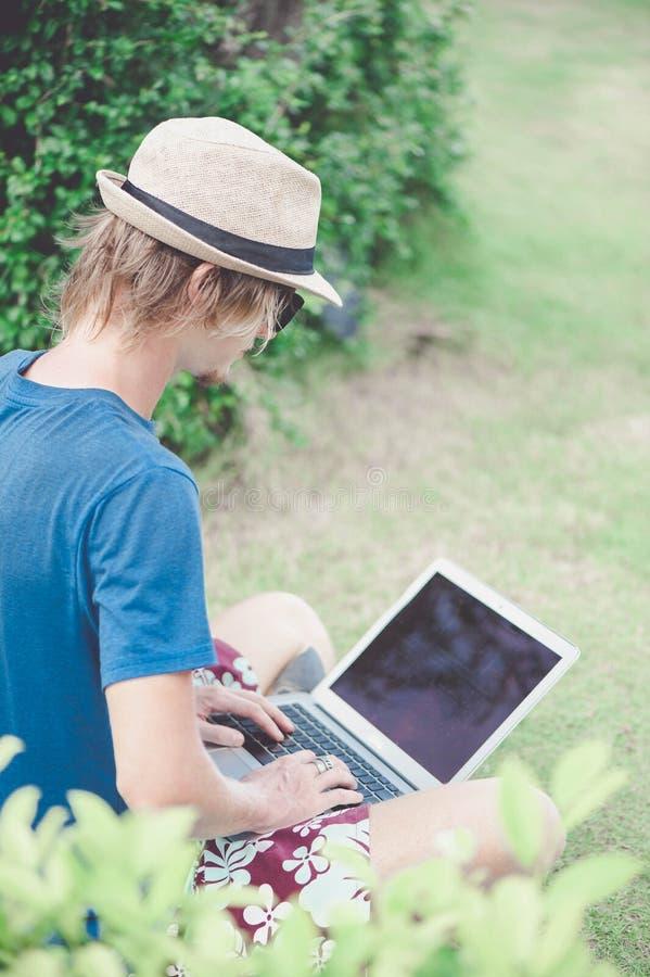 Óculos de sol vestindo do homem louro considerável e um funcionamento do chapéu com o portátil na praia fotografia de stock