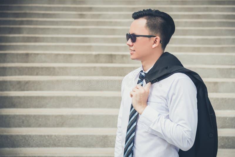 Óculos de sol vestindo do homem de negócios e guardar sui preto foto de stock