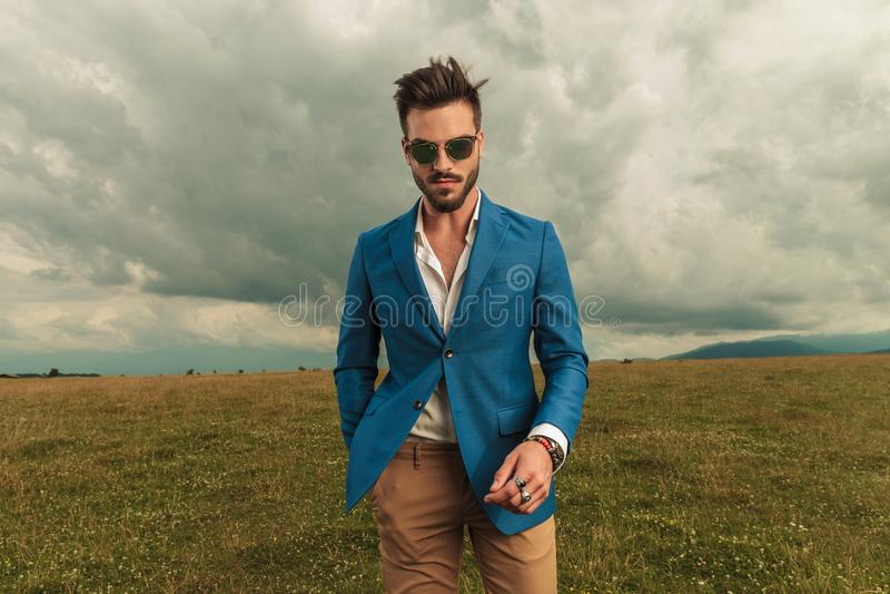 Óculos de sol vestindo do homem relaxado e parte externa ereta do terno azul imagens de stock